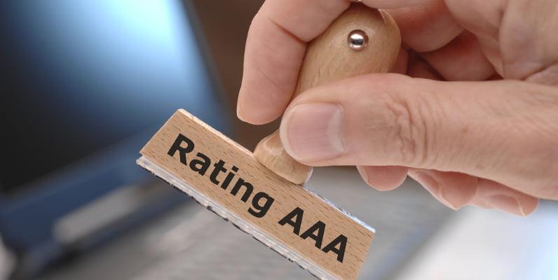 Mano del bancario con timbro che assegna rating a un'azienda